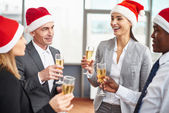 Business partners in Santa caps holding flutes — Stock Photo