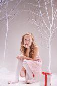 Little girl sitting on giftbox — Stockfoto