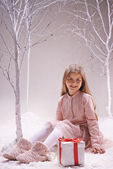 Girl with gift box in winter forest — ストック写真