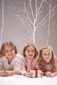 Girls holding giftbox in winter garden — Stockfoto