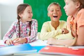 Schoolkids laughing at lesson — Stock Photo