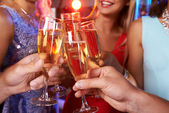 Hands clinking champagne flutes — Stock Photo