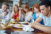 Friends using smartphones at cafe — Foto Stock