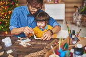 Father and son painting wooden deer — Stock Photo