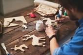 Craftsman painting wooden deers — Stock Photo