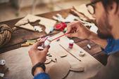 Craftsman painting xmas symbols — Stock Photo