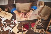 Male hands wrapping Christmas gifts — Stock Photo