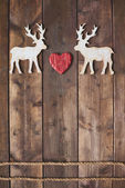 Wooden deer with red heart — Stock Photo