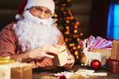 Santa Claus packing presents — Stok fotoğraf