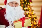 Santa Claus holding golden giftbox — Stock Photo