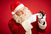 Santa Claus pointing at alarm clock — Stock Photo