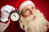 Perplexed Santa holding clock — Stock Photo