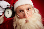 Puzzled Santa holding clock — Stock Photo