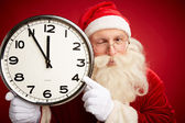 Santa holding clock with five minutes to midnight — Stock Photo