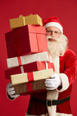 Santa with pile of giftboxes — Stock Photo