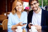 Man and woman with smartphones in cafe — Stock Photo