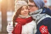 Man kissing his girlfriend on cheek — Stock Photo