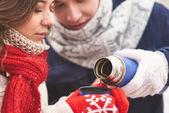 Couple going to drink hot tea in winter — Stock Photo
