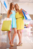 Girls with paperbags in mall — Stock Photo
