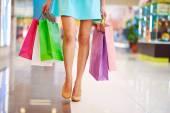Legs of shopaholic girl — Stock Photo