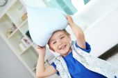 Boy playing with pillow — Stock Photo