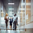 Business peope going along corridor — Stock Photo #62854883