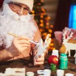 Santa Claus painting wooden deer — Stock Photo #62858845