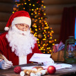 Santa Claus answering Christmas letter — Stock Photo #62858847