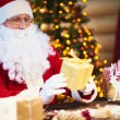 Santa Claus holding golden giftbox — Stock Photo #62858887
