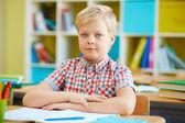 Schoolboy by desk in classroom — Stock Photo