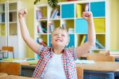 Ecstatic schoolboy in classroom — Stock Photo