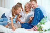 Family on sofa with touchpad — Zdjęcie stockowe
