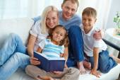 Famaly reading book at home — Stock Photo