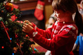 Girl decorating Christmas firtree — Stock Photo