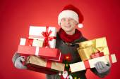 Man in Santa cap holding gifts — Stock Photo