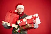 Man in Santa cap holding gifts — Stock Photo
