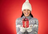 Girl in winterwear looking at small giftbox — Stock Photo