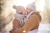 Loving couple kissing in snowfall — Stock Photo