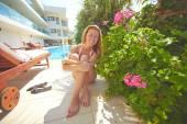 Woman sunbathing by pool — Stock Photo