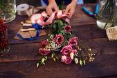 Florist tying rose bunch — Stock Photo