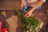 Florist cutting floral stems — Stock Photo