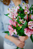 Lilies in female hands — Stock Photo