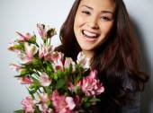 Satisfied woman with flowers — Stock Photo