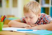 Boy napping by desk — Stock Photo