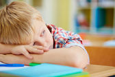 Tired schoolboy having rest — Stock Photo