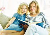 Kid and mother reading book — Stock Photo