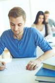 Student ticking right answers — Stock Photo