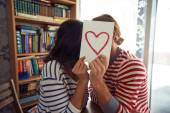 Flirty couple sitting in library — Stock Photo