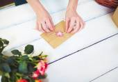 Hands tying love note in envelope — Stock Photo