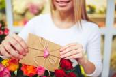 Woman  putting love message in bouquet — Stockfoto